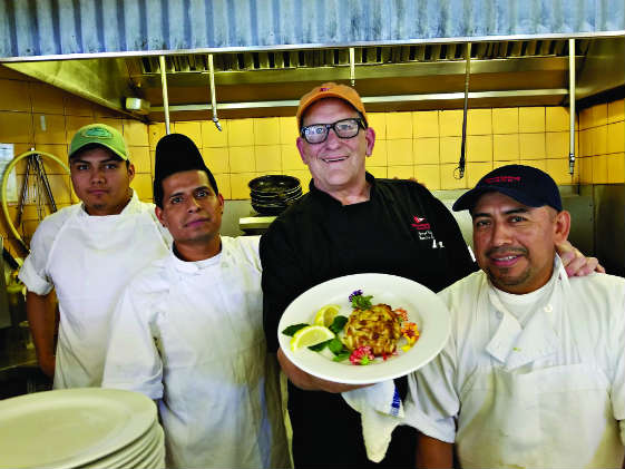 Boatyard Bar & Grill chef George Betz and staff show off a crabcake. Photo by Craig Ligibel
