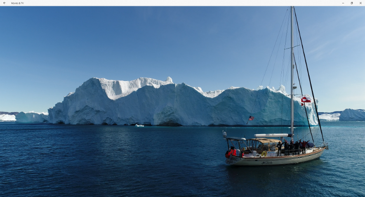 S/V Celebrate sailing in front of an iceberg in Greenland before reaching the NW Passage.