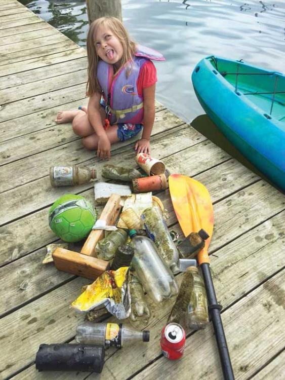 Cindy Wallach trash cleanup with her daughter aboard their kayak