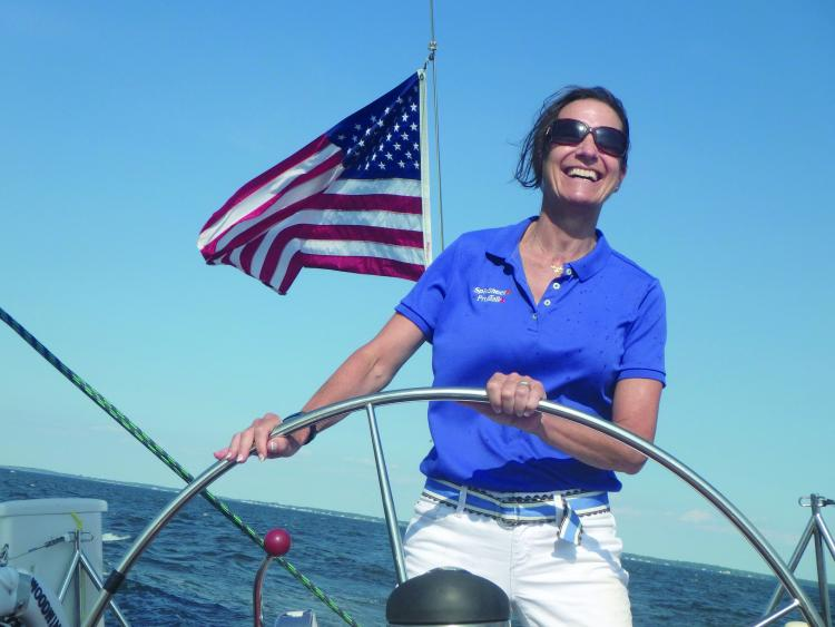 SpinSheet staffer Holly Foster at the wheel aboard the Schooner Woodwind