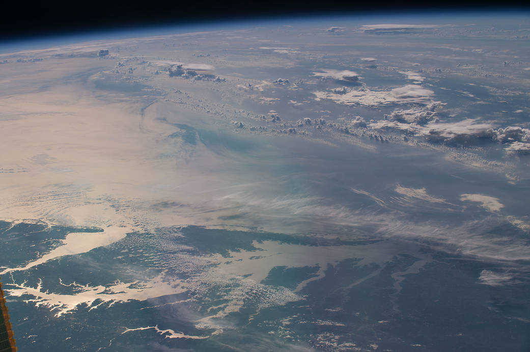 "On July 21, 2016, Expedition 48 Commander Jeff Williams of NASA shared this photograph of sunglint illuminating the waters of the Chesapeake Bay, writing, ""Morning passing over the Chesapeake Bay heading across the Atlantic."" Courtesy of NASA"
