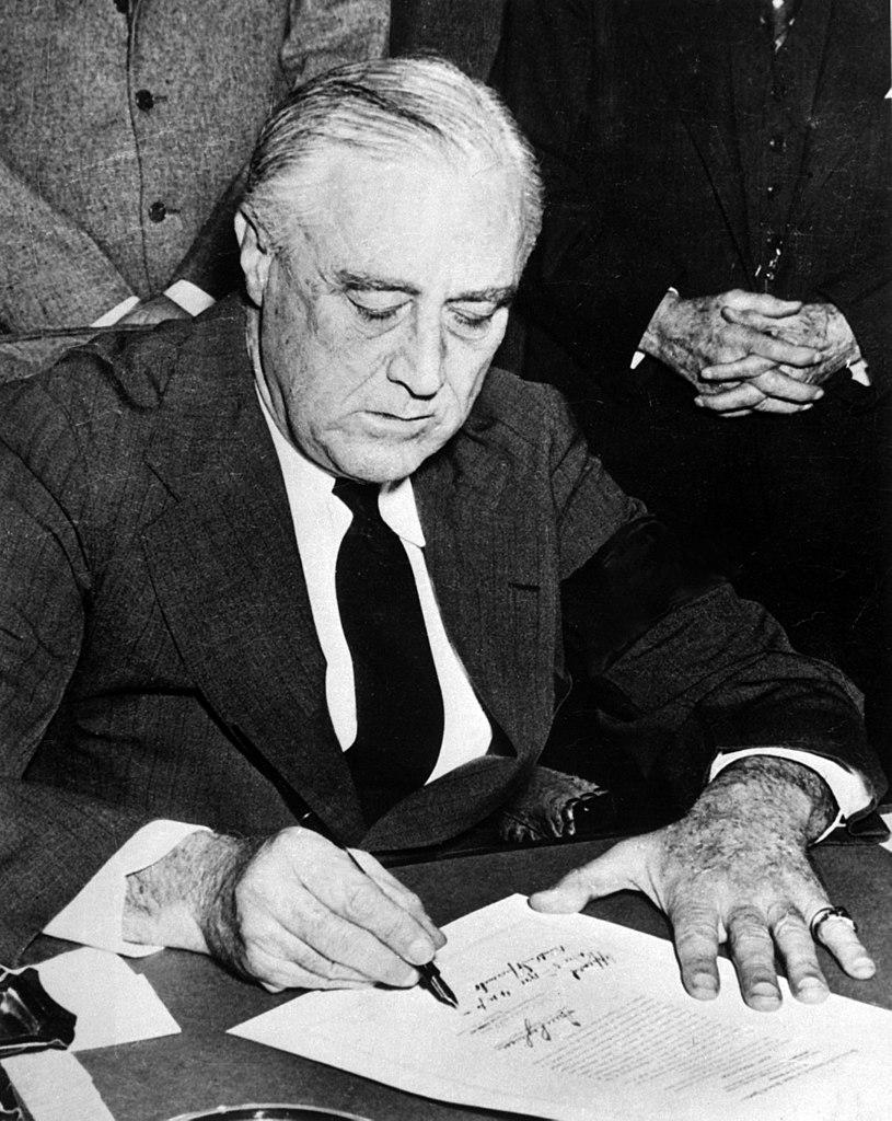 Franklin Roosevelt signing the declaration of war against Japan.
