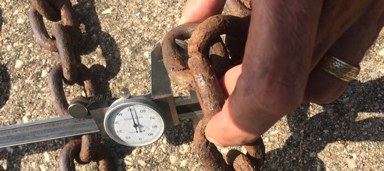 Inspecting chain for wear and tear.
