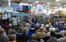 Tucker Thompson speaks in front of a crowd at Fawcett Boat Supplies in Annapolis. Photo by Craig Ligibel