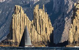 2015 Rolex competitor Ichiban sails down the Tasmanian Coast past a spectacular feature called the Organ Pipes. Photo by Stefano Gattini